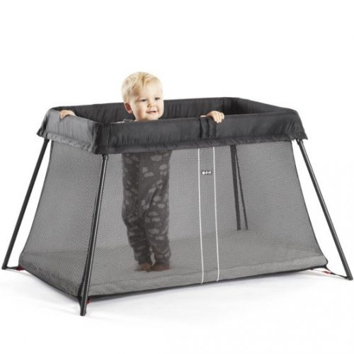 A baby standing inside a Babybjorn Travel Cot Light Black