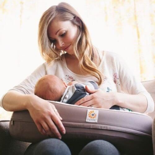 A mom using Ergobaby Natural Curve Nursing Pillow Brown while breastfeeding her baby