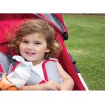 A baby/toddler sitting in a red pram with an orange Cherub Baby Click n Go Travel Bottle Warmer