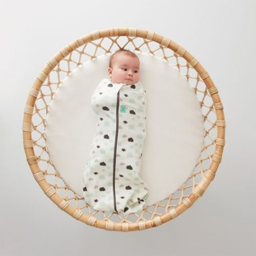 Baby lying on a basket wearing an ergoPouch Cocoon Swaddle Bag (0.2 tog) / ergoPouch Cocoon Swaddle Bag (1.0 tog) in Clouds print