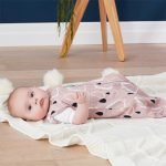 A Baby Lying on the Floor Wearing the Nature Collection Drops ergoPouch Cocoon Bamboo Swaddle Bag (0.2 tog) with Her Arms Out